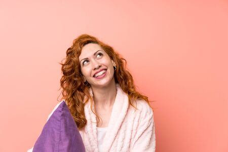Redhead woman in dressing gown laughing and looking up Banque d'images - 129849836