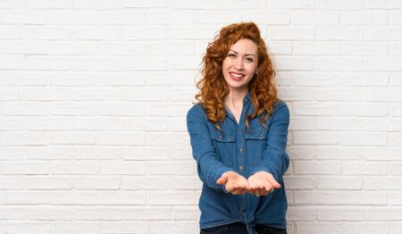 Redhead woman over white brick wall holding copyspace imaginary on the palm to insert an ad