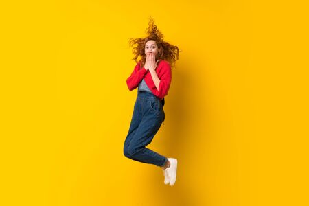 Redhead woman with overalls jumping over isolated yellow wall Stock Photo