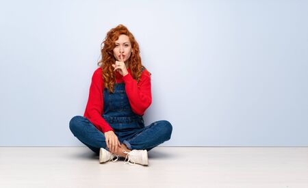 Redhead woman with overalls sitting on the floor showing a sign of silence gesture putting finger in mouth