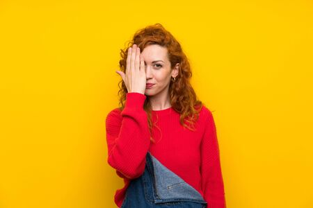 Redhead woman with overalls over isolated yellow wall covering a eye by hand Фото со стока
