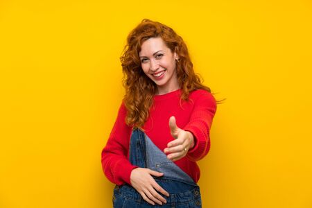 Redhead woman with overalls over isolated yellow wall handshaking after good deal