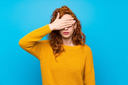 Redhead woman with yellow sweater covering eyes by hands. Do not want to see something