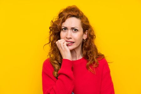 Redhead woman with overalls over isolated yellow wall nervous and scared