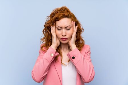 Redhead woman in suit over isolated blue wall with headache