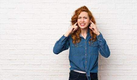 Redhead woman over white brick wall frustrated and covering ears 스톡 콘텐츠