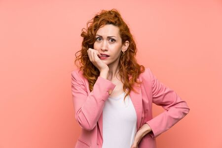 Redhead woman in suit over isolated pink wall nervous and scared 스톡 콘텐츠