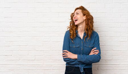 Redhead woman over white brick wall happy and smiling