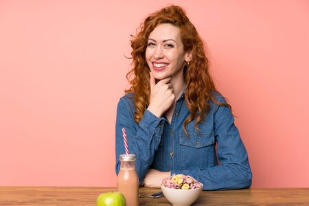 Redhead woman having breakfast cereals and fruit laughing