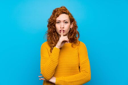 Redhead woman with yellow sweater showing a sign of silence gesture putting finger in mouth 写真素材