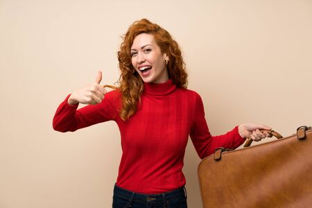 Redhead woman with turtleneck sweater holding a vintage briefcase