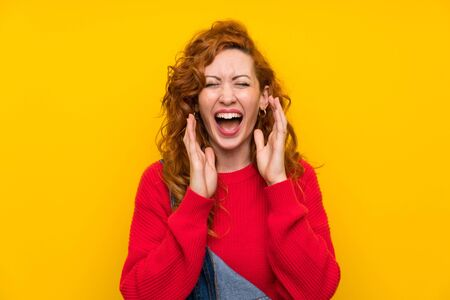 Redhead woman with overalls over isolated yellow wall laughing