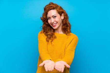 Redhead woman with yellow sweater holding copyspace imaginary on the palm to insert an ad