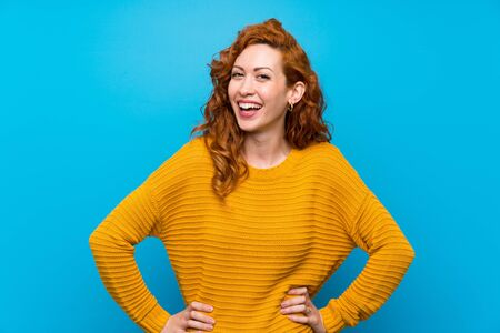 Redhead woman with yellow sweater posing with arms at hip and smiling