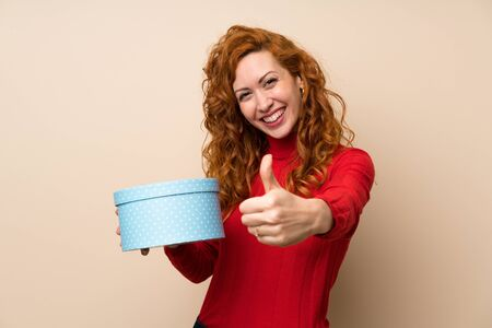 Redhead woman with turtleneck sweater holding gift box Stock fotó