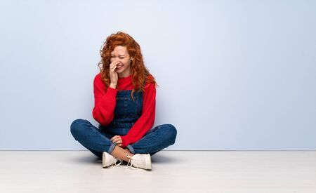 Redhead woman with overalls sitting on the floor smiling a lot