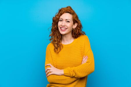 Redhead woman with yellow sweater keeping the arms crossed in frontal position