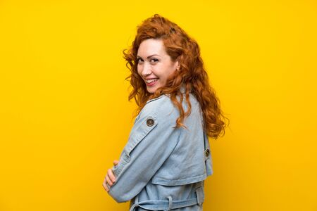 Redhead woman over isolated yellow background laughing Stock fotó