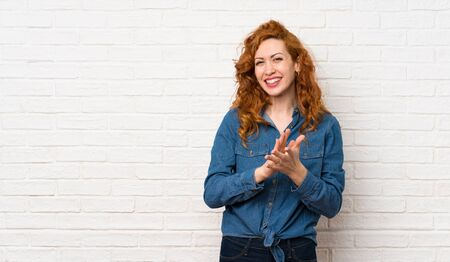 Redhead woman over white brick wall applauding after presentation in a conference