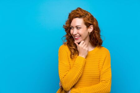 Redhead woman with yellow sweater looking to the side