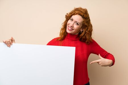 Redhead woman with turtleneck sweater holding an empty white placard for insert a concept Stock fotó