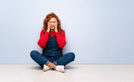 Redhead woman with overalls sitting on the floor with headache