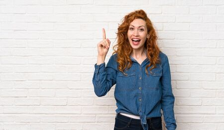 Redhead woman over white brick wall intending to realizes the solution while lifting a finger up