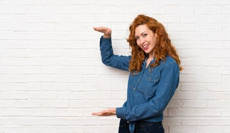 Redhead woman over white brick wall holding copyspace to insert an ad