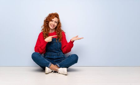Redhead woman with overalls sitting on the floor holding copyspace imaginary on the palm to insert an ad