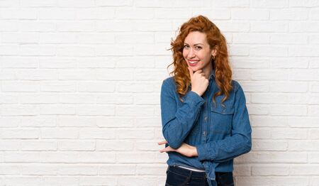 Redhead woman over white brick wall looking to the side