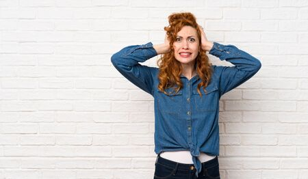 Redhead woman over white brick wall frustrated and takes hands on head