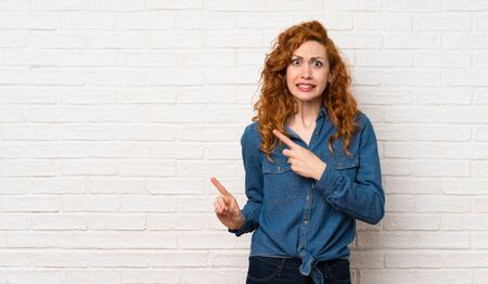 Redhead woman over white brick wall frightened and pointing to the side