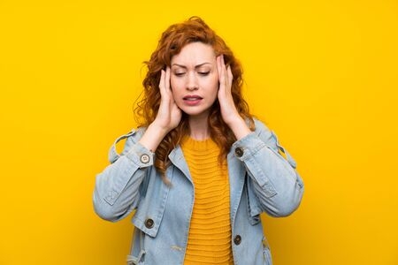 Redhead woman over isolated yellow background unhappy and frustrated with something. Negative facial expression
