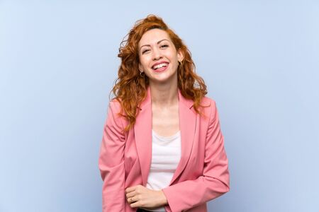 Redhead woman in suit over isolated blue wall smiling