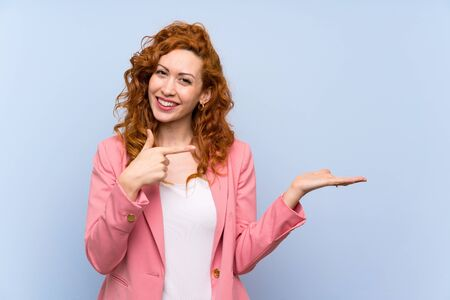 Redhead woman in suit over isolated blue wall holding copyspace imaginary on the palm to insert an ad Stockfoto
