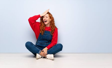 Redhead woman with overalls sitting on the floor has realized something and intending the solution