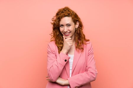 Redhead woman in suit over isolated pink wall laughing