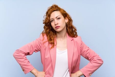 Redhead woman in suit over isolated blue wall angry