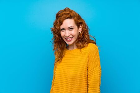 Redhead woman with yellow sweater smiling Stock fotó