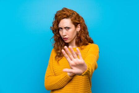 Redhead woman with yellow sweater nervous stretching hands to the front 스톡 콘텐츠