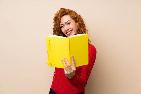 Redhead woman with turtleneck sweater holding and reading a book