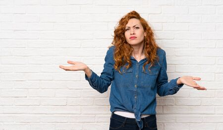 Redhead woman over white brick wall unhappy for not understand something 스톡 콘텐츠