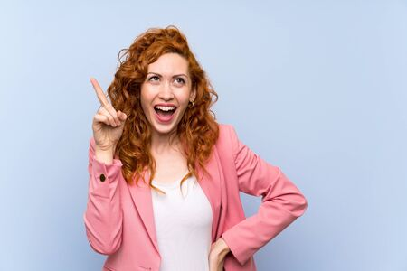 Redhead woman in suit over isolated blue wall intending to realizes the solution while lifting a finger up