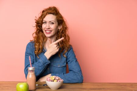 Redhead woman having breakfast cereals and fruit pointing finger to the side