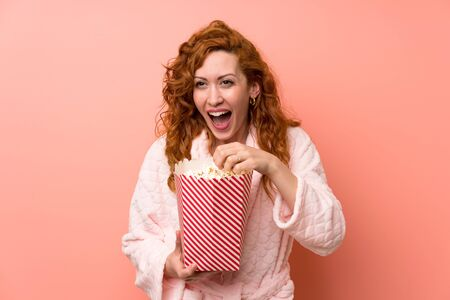 Redhead woman in dressing gown eating popcorns