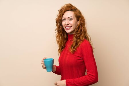 Redhead woman with turtleneck sweater holding hot cup of coffee