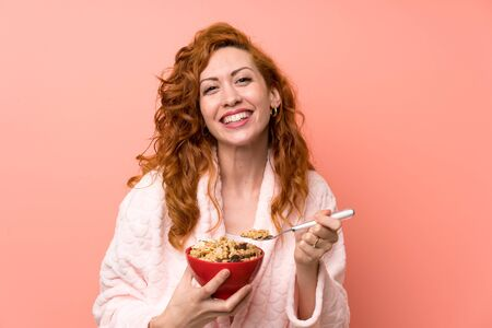 Redhead woman in dressing gown holding a bowl of cereals Stock Photo