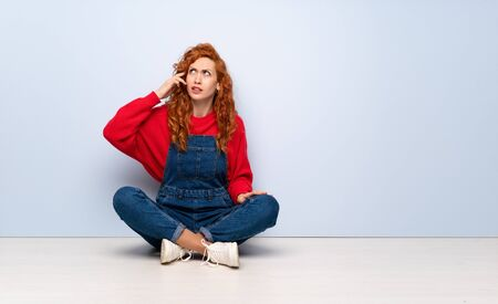 Redhead woman with overalls sitting on the floor with problems making suicide gesture