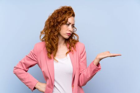 Redhead woman in suit over isolated blue wall holding copyspace with doubts