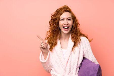 Redhead woman in dressing gown pointing finger to the side Stock fotó